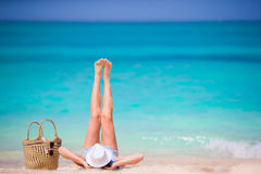 Young beautiful girl relaxing on white beach. Tourist woman enjoy beach vacation lying on the sand Stock Photo
