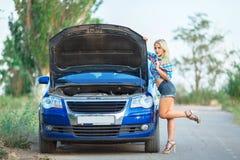 Young beautiful girl repairs blue car stock photography