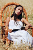 Young beautiful girl resting in a chair in the field of wheat Royalty Free Stock Images