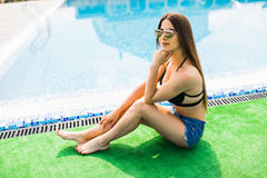 Young beautiful girl resting in the swimming pool. Summer time Royalty Free Stock Image