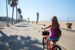 Young beautiful girl riding a bike down the Venice beach. In Los Angeles Royalty Free Stock Photo