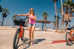 Young beautiful girl riding a bike down the Venice. Beach in Los Angeles. Californian dreaming royalty free stock image