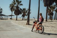 Young beautiful girl riding a bike down the Venice. Beach in Los Angeles Californian dreaming stock photography