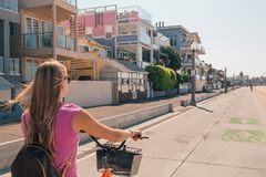 Young beautiful girl riding a bike down the Venice. Beach in Los Angeles. Californian dreaming stock photo