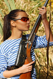 Young beautiful girl with a rifle hunts in the reeds. Stock Image