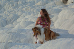 Young beautiful girl with rough collie dog looking aside sitting on white rock Stock Photography