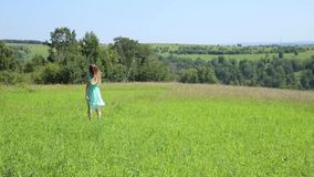 Young beautiful girl running on the green field stock video