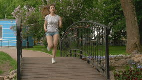 A young beautiful girl runs across the bridge of love to boyfriend. Date of the couple. stock video footage
