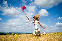 Young beautiful girl runs in wheat Royalty Free Stock Image