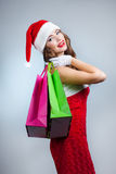Young beautiful girl in santa hat with shopping bags Stock Photo