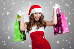 Young beautiful girl in santa hat with shopping bags Royalty Free Stock Image