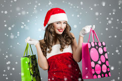 Young beautiful girl in santa hat with shopping bags Stock Images