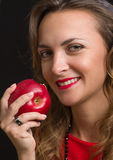 The young beautiful girl in a scarlet dress eats apple Stock Image