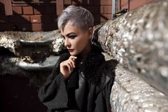 Young beautiful fashion girl shooting outdoors near brick wall at house. Young beautiful girl with short gray hair in a black jacket and aggressive leather boots stock photo