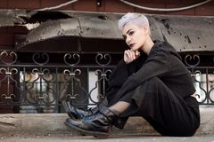 Young beautiful fashion girl shooting outdoors near brick wall at house. Young beautiful girl with short gray hair in a black jacket and aggressive leather boots royalty free stock photo