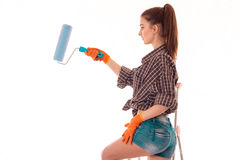Young beautiful girl in short shorts holding a roller for painting turning sideways Stock Image