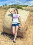 Young beautiful girl in short shorts standing in a field based on a round bale of hay and looks into the distance. Summer hot sunny day. The season of harvest royalty free stock image