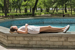 Young beautiful girl in short white dress lies near fountain Stock Images