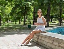 Young beautiful girl in short white dress sit near fountain Stock Photos