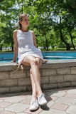 Young beautiful girl in short white dress sit near fountain Royalty Free Stock Photo
