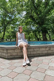 Young beautiful girl in short white dress sit near fountain Royalty Free Stock Images