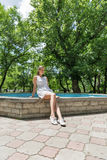 Young beautiful girl in short white dress sits near fountain Stock Photography