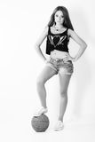 Young beautiful girl in shorts with the ball stands in the Studio on the white background Stock Photo