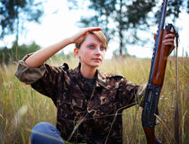 Young beautiful girl with a shotgun looks into the Royalty Free Stock Photography