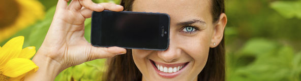 Free Young Beautiful Girl Showing Your Smartphone Screen Royalty Free Stock Image - 77545726