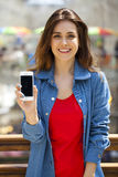 Young beautiful girl showing your smartphone screen Royalty Free Stock Photography