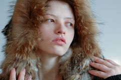 Young beautiful girl shows the photographer part of her cute young body. Jacket of wolf fur.  Stock Image