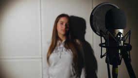 Young beautiful girl sings.Young singer singing into a microphone.Portrait close up of the singer.Recording studio Stock Photography