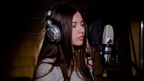 Young beautiful girl sings.Young singer singing into a microphone.Portrait close up of the singer.Recording studio stock footage