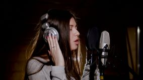 Young beautiful girl sings.Young singer singing into a microphone.Portrait close up of the singer.Recording studio Royalty Free Stock Photo