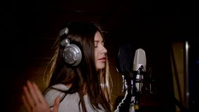 Young beautiful girl sings.Young singer singing into a microphone.Portrait close up of the singer.Recording studio Stock Photos
