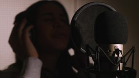 Young beautiful girl sings.Young singer singing into a microphone.Portrait close up of the singer.Recording studio Stock Photo