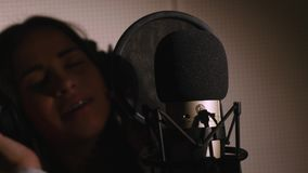 Young beautiful girl sings.Young singer singing into a microphone.Portrait close up of the singer.Recording studio Royalty Free Stock Photos
