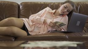 Young beautiful girl sit in leather sofa talking by mobile phone, looking at computer and counting money cash. Work in internet for kids stock video footage