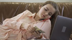 Young beautiful girl sit in leather sofa talking by mobile phone, looking at computer and counting money cash stock video footage