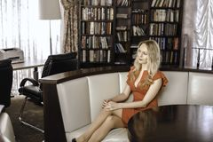 Young beautiful girl sit in a luxury living room stock image