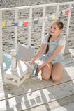 A young beautiful girl sits on the beach keeps toys and smile. Under the sun Stock Photos