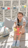 A young beautiful girl sits on the beach keeps toys and smile. Under the sun Royalty Free Stock Photos