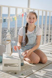 A young beautiful girl sits on the beach keeps toys and smile. Under the sun Royalty Free Stock Images