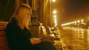 Young beautiful girl sits on a bench in a night park and using a tablet. Alley and lights in the background. Close up.  stock video