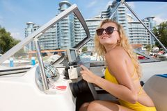 A young, beautiful girl sits at the helm of the yacht royalty free stock photo