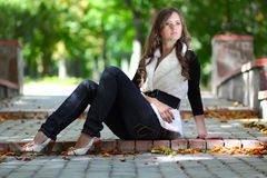 Young beautiful girl sits in park Stock Photos