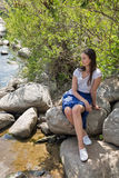 Young beautiful girl sits on a rock on riverbank Royalty Free Stock Photos