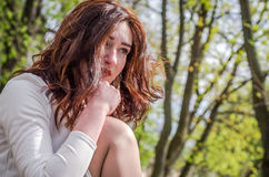 Young beautiful girl sits sad in a white dress in a street in the spring city of Lviv Stock Photo