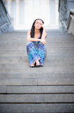 Young beautiful girl sits on steps Royalty Free Stock Image