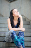 Young beautiful girl sits on steps Royalty Free Stock Images